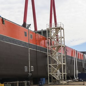 Picture 11 - The assembled hull of the Caribbean FLNG at the Wison yard. The weld seams and some repair where hot work has been done need to be coated as the final step of completing the hull coating.