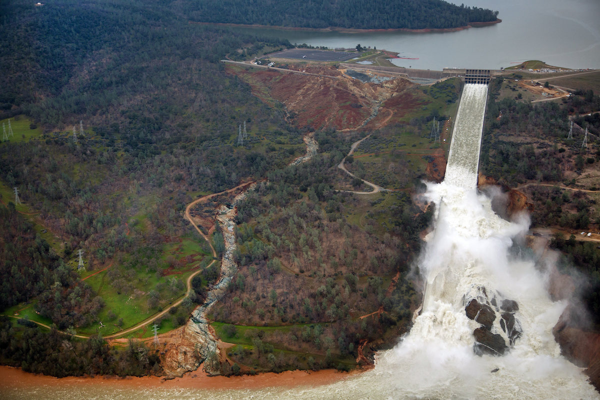 This aerial view looks east toward Oroville Dam and Lake Oroville, showing the damaged spillway with its outflow of 100,000 cubic feet per second (cfs) at the Butte County site. The California Department of Water Resources has a goal to lower the lake level by 50 feet to handle the next round of winter storms. Photo taken February 15, 2017. Dale Kolke / California Department of Water Resources